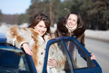 Two young women with car in winter day Stock Photo - 8996950