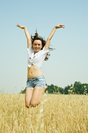 Jumping girl  at cereals field in summer photo