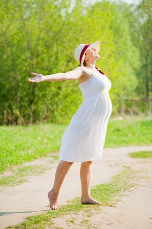 spring hat: Portrait of 6 months pregnant woman in sunny day