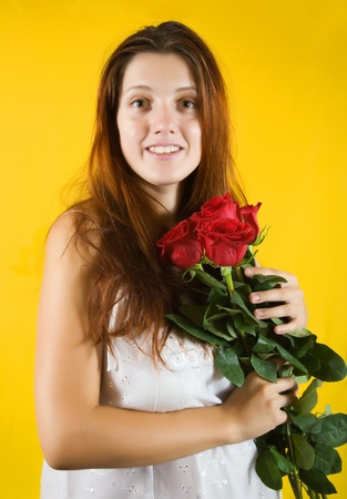 Portrait of   girl with roses over yellow background photo