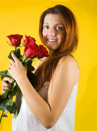 beauty  girl with roses  on yellow background photo