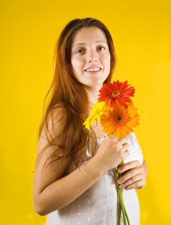 Portrait of tender girl with flowers over yellow background photo