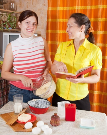douther: Two women making Easter cake with  cookbook  in the kitchen at home