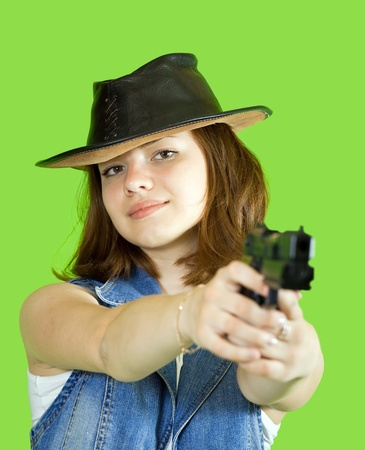 Pretty girl  aiming a black gun over green photo