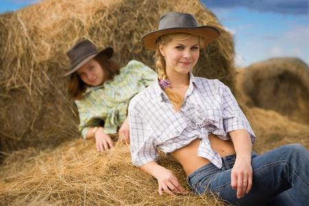 girls on fresh hay at field photo