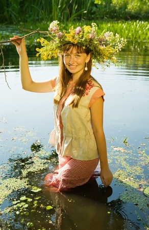 girl  in russian traditional clothes in river photo