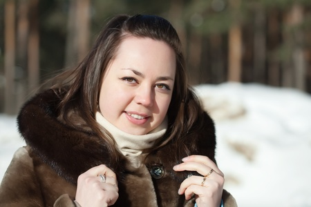 Outdoor winter portrait of girl in wintry clothes photo
