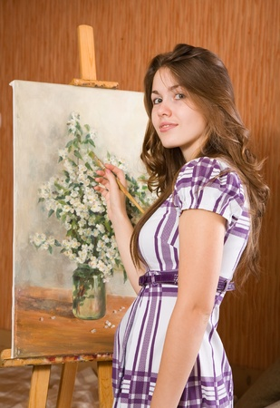 Female painter with brushes near  easel with picture of flowers in interior Stock Photo - 9059115