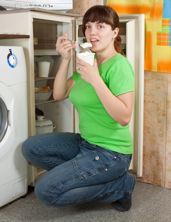 whig: Young woman eating  yoghurt from refrigerator at home Stock Photo