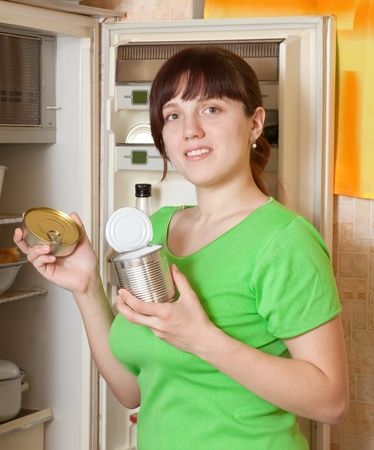 Young woman putting with metal can near refrigerator  at home Stock Photo - 9060676