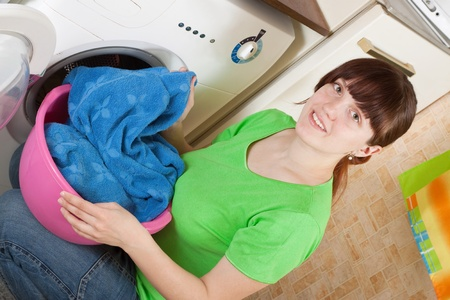 Young woman putting clothes in to washing machine and smiling photo