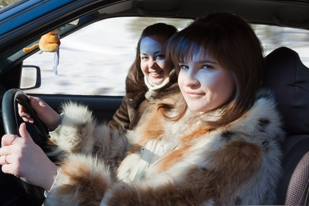 two wheel: Two young women in fur coat is driving  car