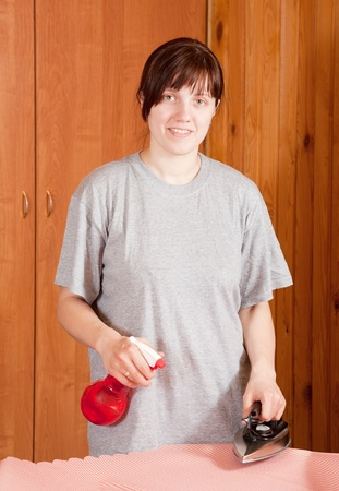 Happy young woman ironing a fabric at home photo