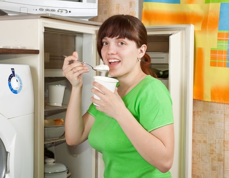 whig: Young woman eating  dairy cream from  fridge  at home