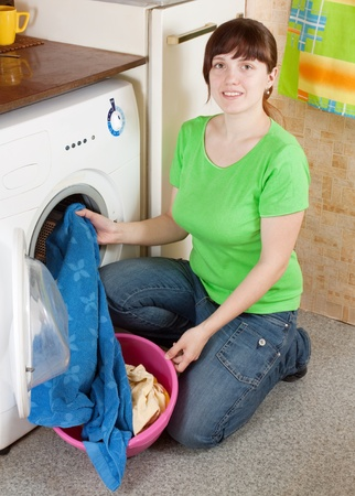 Young woman putting clothes into washing machine and smiling photo