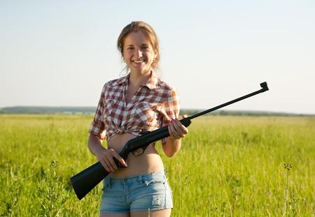 rifleman: beautiful girl holding pneumatic air rifle outdoor
