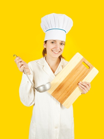 young woman in chef uniform tasting from ladle over yellow background photo