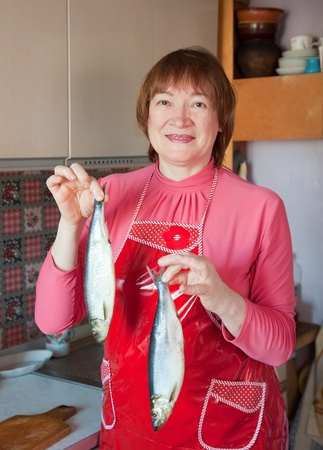 Mature woman in her kitchen with salty herring in hands photo