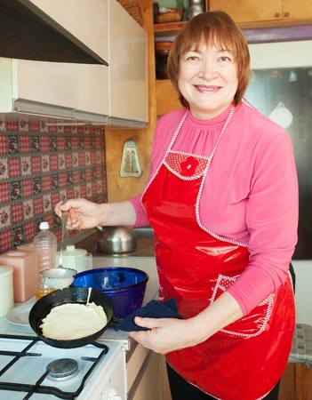 fryingpan: Mature woman bakes pancakes at her kitchen