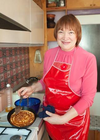 fryingpan: Mature woman cooking pancakes at her kitchen