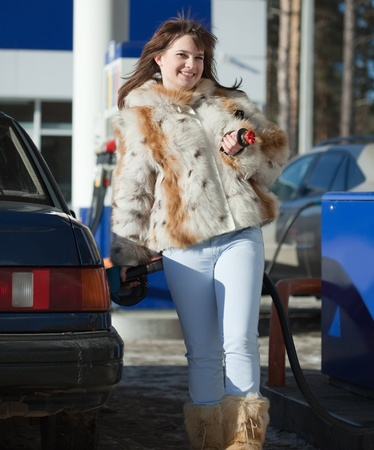 Young  woman filling her car in winter photo