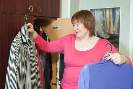 Mature woman at wardrobe. She thinking what get dressed. photo
