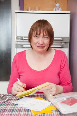 Sad mature woman with utility bills  at her home Stock Photo - 9109462