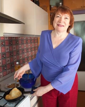 Mature woman cooking pancake at her kitchen Stock Photo - 9109469
