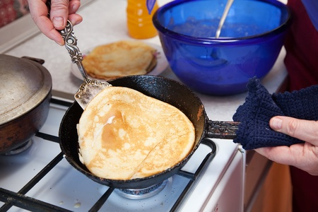 Cook hands cooking pancakes on griddle photo