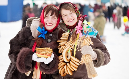 sudarium: Happy girls in russian traditional clothes with pancake and round cracknel during  Shrovetide
