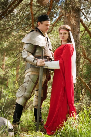 knight in armour and woman in forest photo