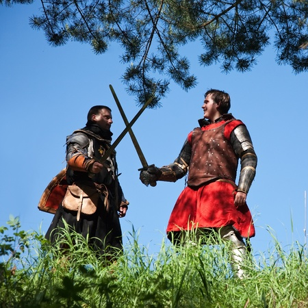 duelling: Two knights in armor is fighting  against sky Stock Photo