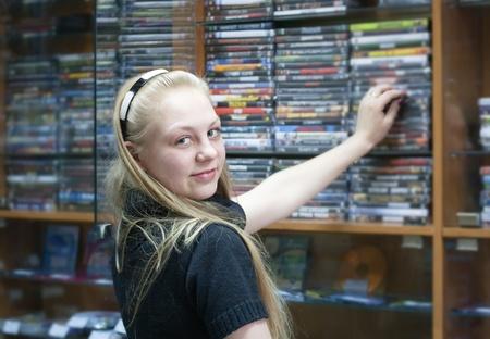 Girl in shop chooses CD or DVD disk photo