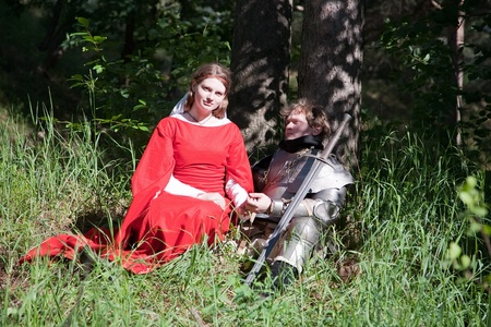 knight in armour and maid in forest photo