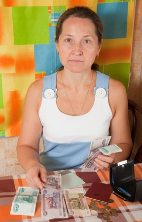 lamentable: thoughtful mature woman with money at her home
