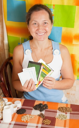 Mature woman with  various seeds at home photo