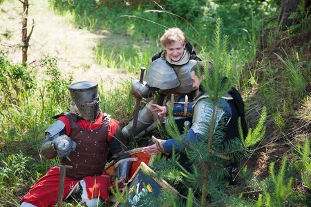 Knights in armour having bivouac at forest photo