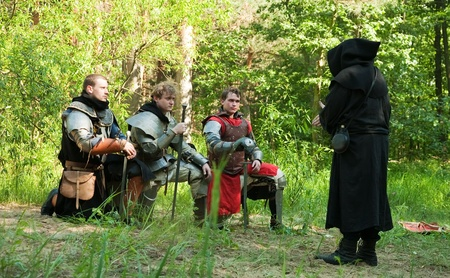 chaplain: before fight. Pray of knights in medieval armours before chaplain