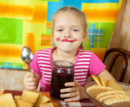 Little girl eating jam from  jar at kitchen Stock Photo - 9167398