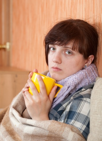 Young illness woman drinking tea in  blanket photo