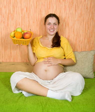 Beautiful and healthy pregnant woman with  fruits photo