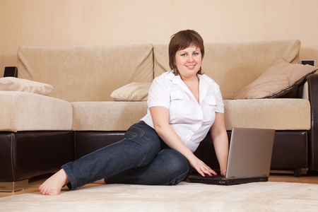 young woman sitting on floor and using laptop Stock Photo - 9167488