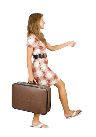 Girl  walking with suitcase. Isolated over white background photo