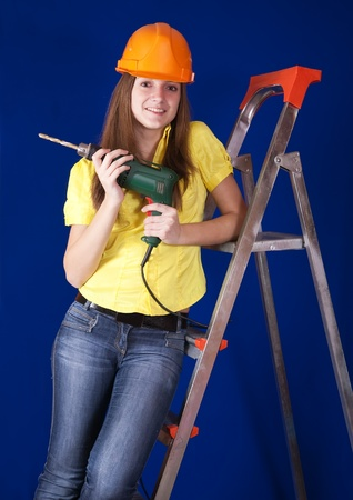 Female construction worker in a hard hat with drill on stepladder photo