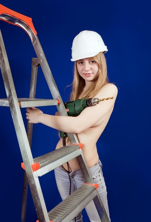 Sexy girl  with drill near stepladder over blue photo