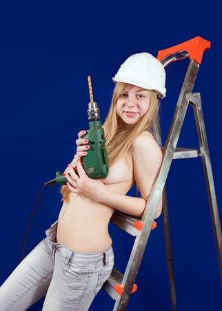 Sexy girl  with drill on stepladder over blue photo
