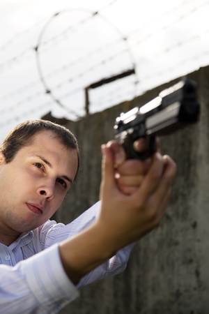 young man aiming a black gun against the prison wall Stock Photo - 9211034