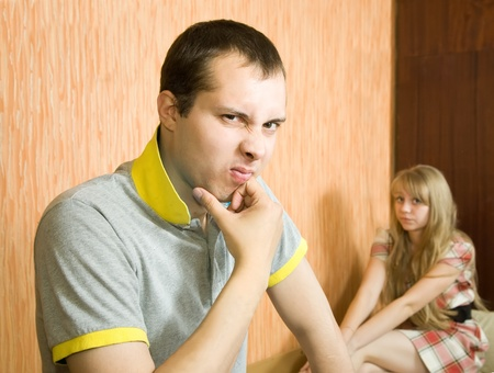 young couple after quarrel inside. Focus on man only Stock Photo - 9235075