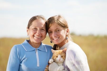Happy mother with her daughter is holding cat against nature photo