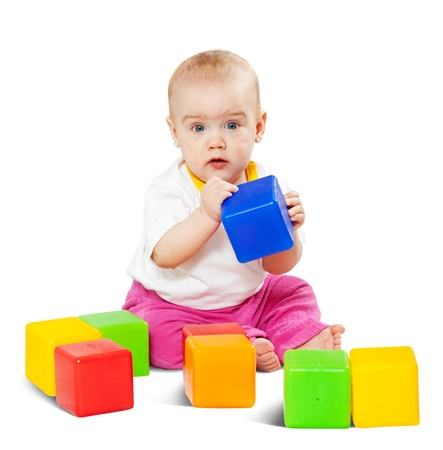Happy baby plays  with toy blocks over white background photo
